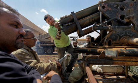 Libyan rebels prime a rocket launcher in Benghazi