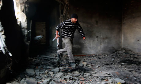 A rebel fighter runs for cover inside a building on the frontline in Tripoli street