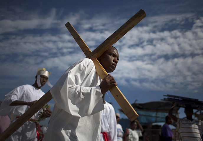 一名扮演耶稣的演员扛着木头十字架重演耶稣逾越