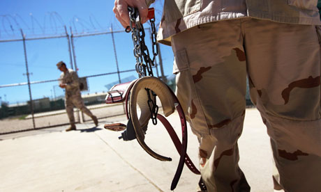 A guard holding leg shackles at Guantnamo Bay