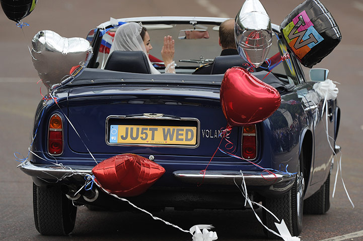 Wedding procession: The couple wave to the crowds in an open-top Aston Martin Volante