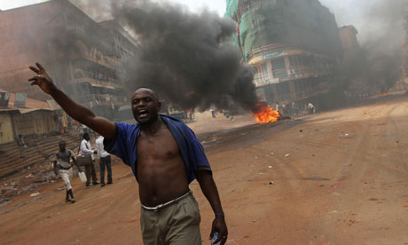 A Ugandan protestor shouts near a burning barricade in Kampala