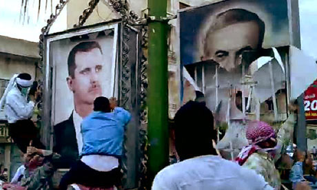 Syrian anti-government protesters tearing down a portrait of late president Hafez al-Assad