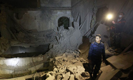 A police officer looks at a damaged building at the High Commission for Children, which the Libyan government said was caused by coalition air strikes, in Tripoli