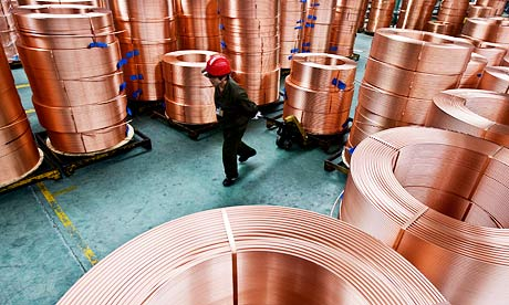 Factory worker moves brass tubes
