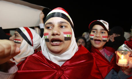 Syrian women living in Jordan paint their face with the Syrian national flag in Amman