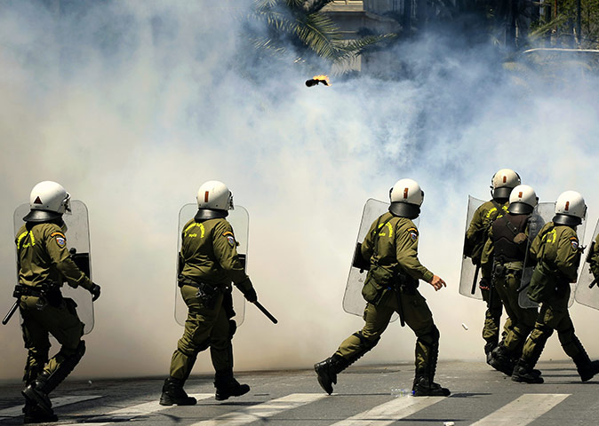 Protests in Athens: A group of riot policemen run through a cloud of teargas