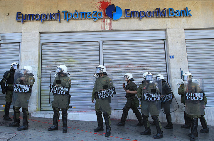 Protests in Athens: Riot policemen stand on duty in front of a bank during violent clashes