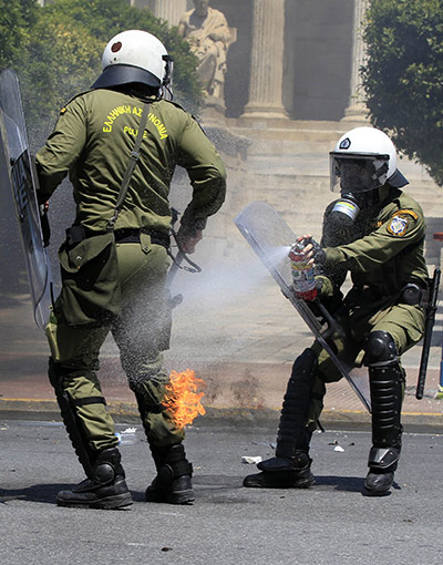 Protests in Athens: A riot policeman extinguishes a fire on a colleague caused by a petrol bomb