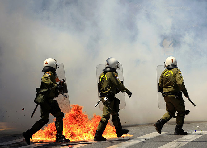 Protests in Athens: Riot policemen run through a cloud of teargas to avoid a petrol bomb