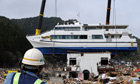 Cranes lift a boat off a two-storey building in the tsunami-devastated town of Otsuchi, Japan
