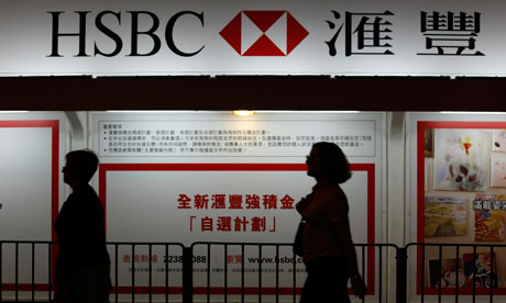 Passers-by walk in front of a HSBC advertisement displayed outside its headquarters in Hong Kong