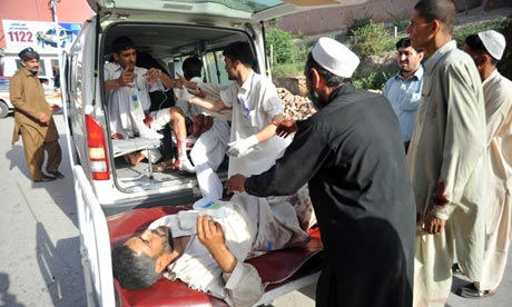 Pakistani paramedics help injured blast victims as they arrive at a hospital in Peshawar