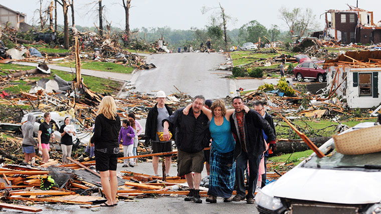 US tornado: Residents in Joplin help a woman after a tornado hit