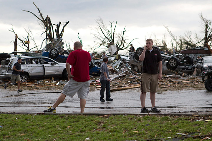 US tornado: People stand near damaged vehicles along Rangeline road in Joplin, Missouri