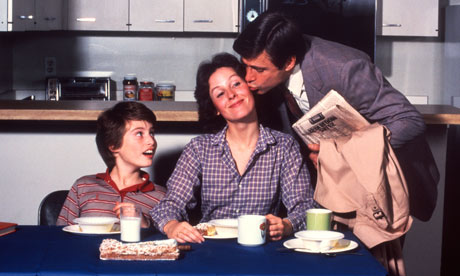 1970s DAD KISSING MOTHER ON CHEEK SURPRISED BOY AT BREAKFAST TABLE
