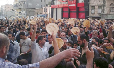 Syrian men hold up pieces of bread as they protest in Banias in solidarity with compatriots in Deraa