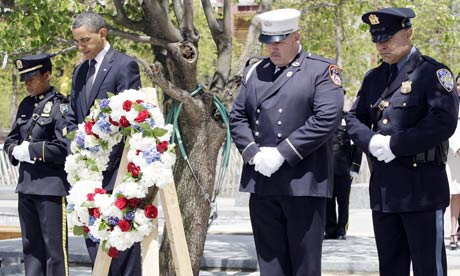 Barack Obama stands with New York fire and police officers after laying a wreath at Ground Zero