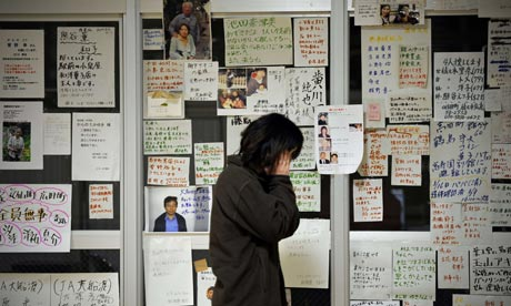 A tsunami survivor is overcome before messages at a relief centre, Rikuzentakata, 22 March.