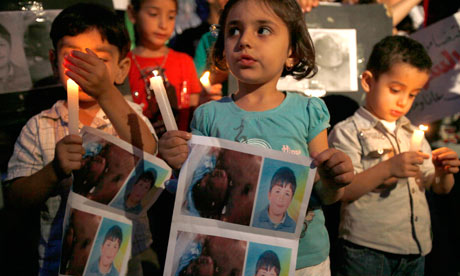 Syrian children carry pictures of Hamza al-Khatib