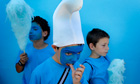 Children eat candy floss while dressed up like smurfs in Juzcar