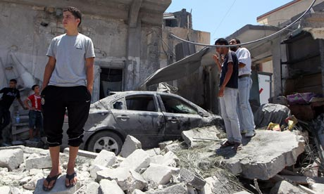 Libyan youths stand on rubble of a house burying a destroyed car in Tripoli