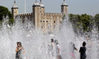 Children play in a fountain in sight of the Tower of London on Monday.