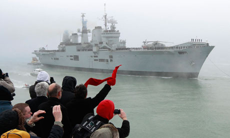 Crowds wave to the aircraft carrier HMS Ark Royal