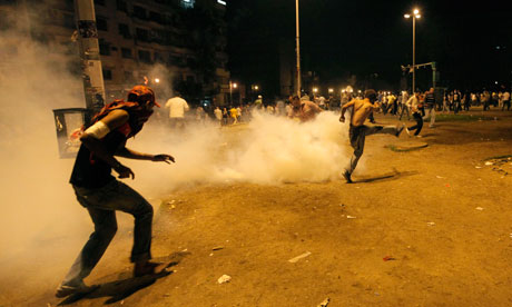An Egyptian protester kicks a tear gas canister during clashesin Tahrir Square, Cairo