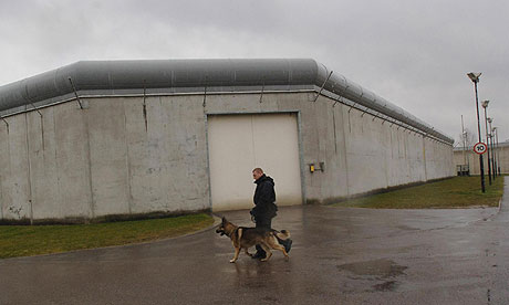 A prison dog handler patrols the grounds of Belmarsh jail