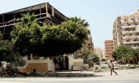 A Libyan man walks past a damaged conference hall often used by the Libyan government