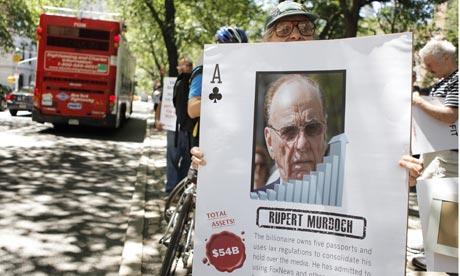 A demonstrator in New York holds a sign denouncing  Rupert Murdoch