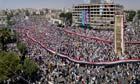 Syrian protesters carry a giant national flag during a rally in al-Assy square, Hama, Syria