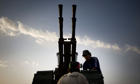 A Libyan rebel fixing an anti-aircraft gun