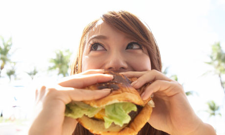 A woman tucks into a hamburger