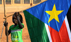 A young girl holds a South Sudan flag