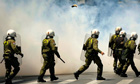 Riot policemen in a cloud of teargas in Athens