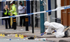 A forensics officer inspects the scene where three men were killed in Winson Green, Birmingham