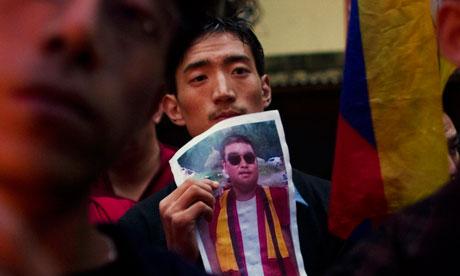 A Tibetan exile holds a portrait of Tsewang Norbu