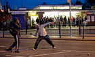 Youths throwing bricks at police on 7 August during unrest in Enfield, north London