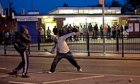 Jovens jogando tijolos contra a polícia em 07 de agosto, durante distúrbios em Enfield, norte de Londres