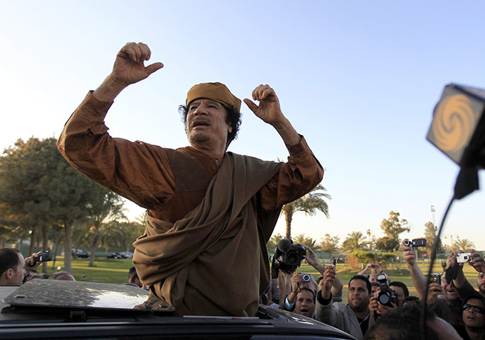 Gaddafi: 10 April 2011: Libyan leader Muammar Gaddafi cheers his supporters