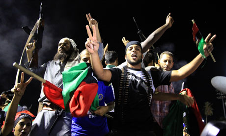 Rebel fighters in Libya celebrate the capture of Muammar Gaddafi's compound