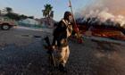 A rebel fighter displays a looted golden gun, Bab al-Aziziya in Tripoli