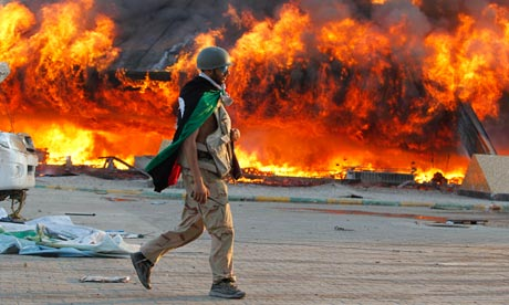 A Libyan rebel walks past flames at the Bab Al-Aziziya compound