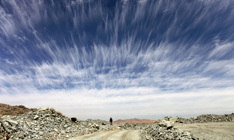 A man walks beneath an unusual cloud formation