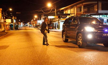 A policeman approaches a vehicle for questioning after curfew hours in Trinidad and Tobago.  (Image Courtesy of The Guardian)