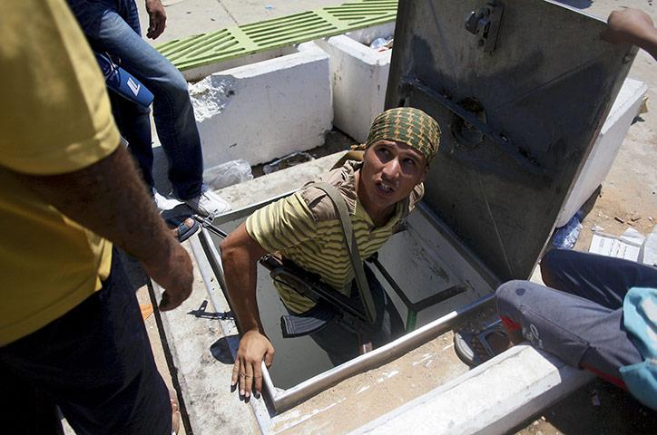 Bab al-Aziziya, Tripoli: A Libyan rebel enters a tunnel, Bab al-Aziziya compound