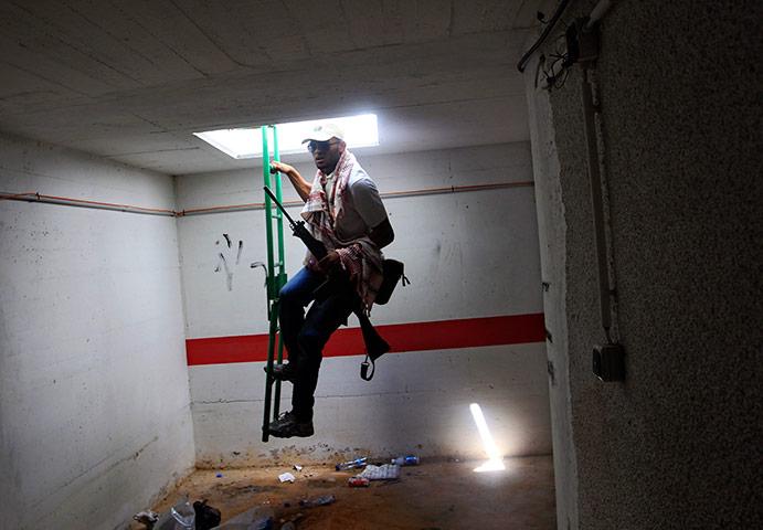 Bab al-Aziziya, Tripoli: A rebel fighter enters a bunker, Bab al-Aziziya compound