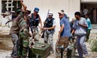 Libyan rebel fighters loot weapons from a military compound in Tripoli